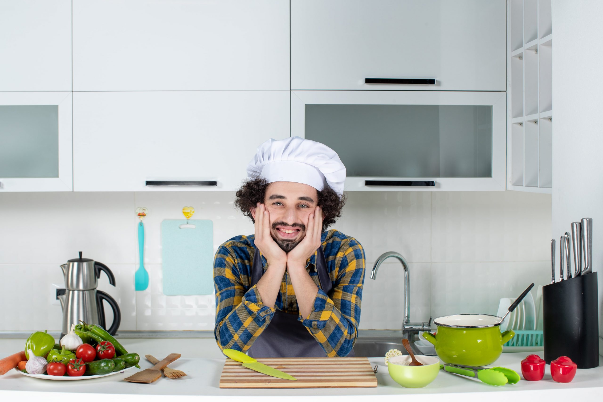 smiling-male-chef-with-fresh-vegetables-posing-white-kitchen